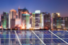 Blue Solar Cell Panels, Blurred City Skyline Illuminated At Night In The Background