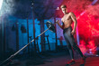 canvas print picture Caucasian muscular shirtless bodybuilder, posing with weight plate flexed on iron bar over smoky dual color background. Weightlifting training.