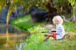 Leinwandbild Motiv Boy fishing. Child with rod catching fish in river