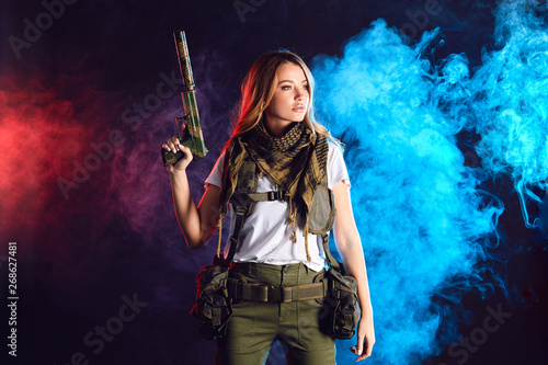 Photo  Special Troops woman soldier in military uniform and protective headphones developing her shooting skills over dark smoky background