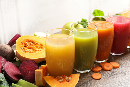Photo Stands Juice Glasses with different juices and fresh ingredients on wooden table
