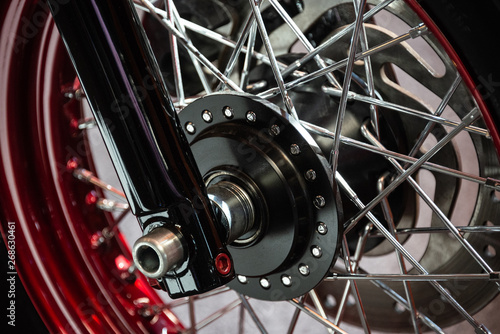Fotografía  Detail of the black wheel of a customized motorcycle chromed with red and silver