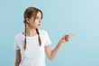 canvas print picture - Young pretty girl with two braids in white t-shirt dreamily looking aside showing with index finger at empty space over blue background isolated