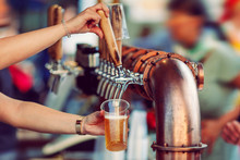 Beer Tapping With Traditional Taps Into A Plastic Cup And Colorful  Blurred Background