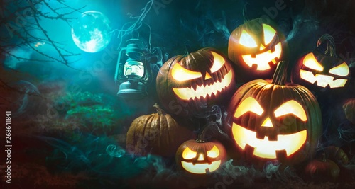Fototapeta Halloween pumpkin head jack lantern with burning candles