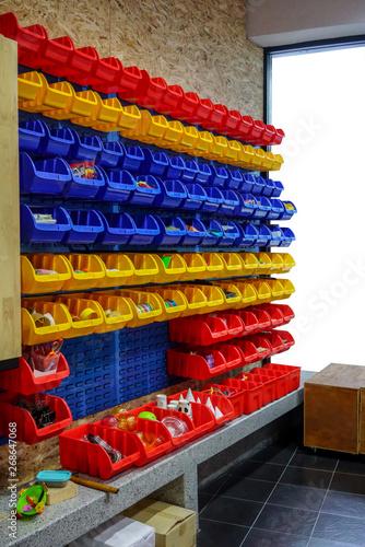 Obraz na plátně  colorful plastic multi-purpose shelf hanging on wooden wall.
