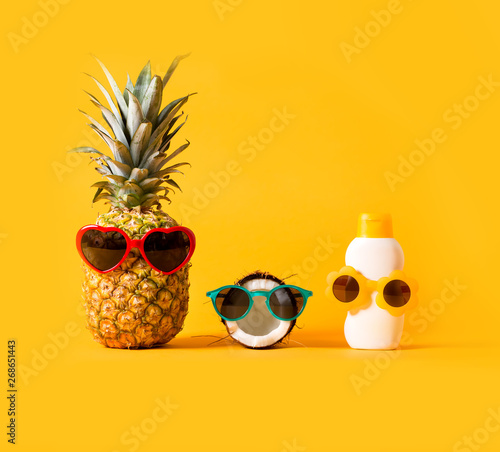Papiers peints Magasin de musique Pineapple and coconut wearing sunglasses with sunblock on a solid background