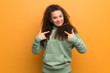 Teenager girl over ocher wall with surprise facial expression