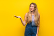 Leinwandbild Motiv Young blonde woman with overalls over isolated yellow background holding copyspace imaginary on the palm