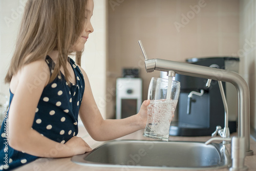 Obraz Portrait of a little caucasian girl gaining a glass of tap clean water. Kitchen faucet. Cute curly kid pouring fresh water from filter tap. Indoors. Healthy life concept - fototapety do salonu