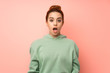 Young redhead woman with sweatshirt with surprise facial expression