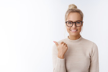 Cose-up Shot Of Upbeat Good-looking Cheerful Young Female In Glasses With Bun Hairstyle Having Awesome Mood Pointing Left And Up With Thumb As Introducing Cool Promotion Over White Wall
