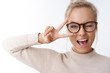 Hey smile you. Portrait of cheeky and cute glamour blond woman in glasses combed hair and sweater winking happily showing peace victory gesture as fooling around, being optimistic