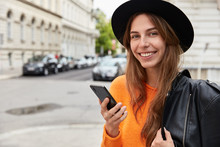 Lovely Positive Female Model Wears Black Hat, Orange Sweater, Has Leather Jacket On Shoulder, Holds Smart Phone While Waits For Call, Smiles Positively At Camera, Enjoys Wandering In Big City