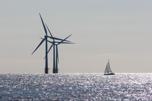 Wind Power. Environmentally Friendly Sailing Yacht. Offshore Windfarm Turbines. Clean Energy.