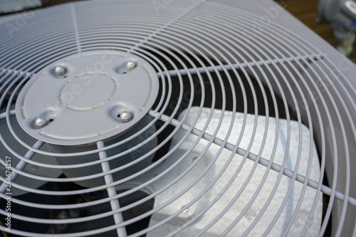 Photo Residential air conditioning unit outdoors with fan and coils