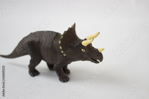 Plastic toy dinosaurs on a light background