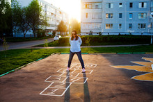Cute Girl Playing Hopscotch. Sunset. Beautiful Summer, Rest After Work In The Courtyard Of A Multi-storey Building