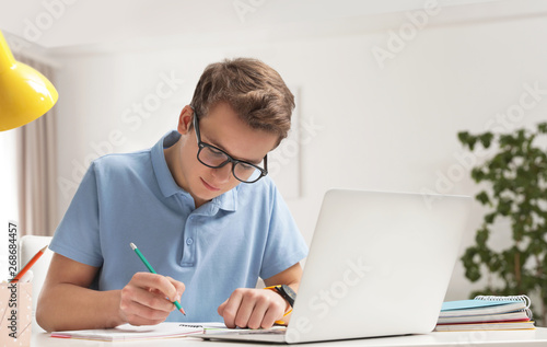 Tela Teenager boy doing his homework at desk indoors