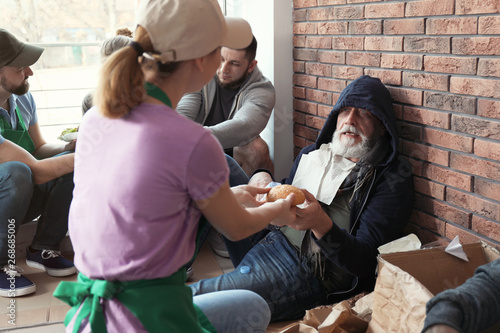 Volunteer giving food to poor senior man indoors Fototapeta