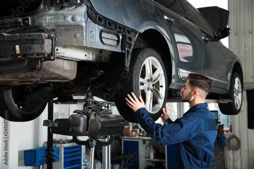 Fotografía  Technician checking car on hydraulic lift at automobile repair shop