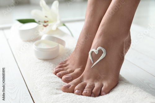 Foto auf Gartenposter Pediküre Woman with beautiful feet and cream on white towel, closeup. Spa treatment