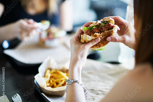 Fototapeta woman eating eating vegan meatless burger in restaurant obraz