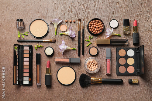 Fototapeta  Many different makeup products and spring flowers on color background, flat lay
