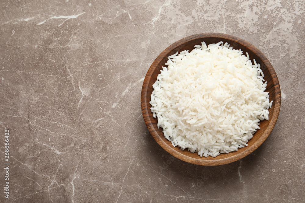 Fototapeta Plate of tasty cooked rice on color background, top view. Space for text