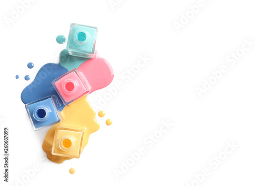 Fotomural Spilled different nail polishes with bottles on white background, top view