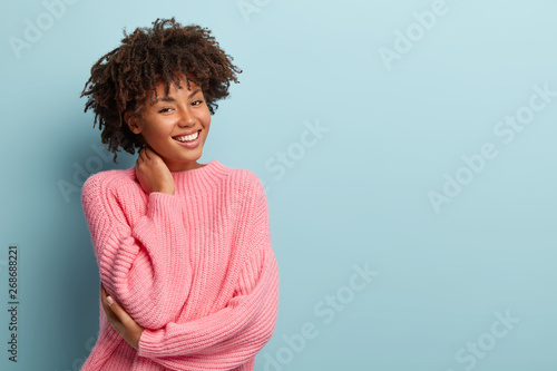 Canvastavla  Studio shot of glad charming young female with Afro haircut, touches neck, wears oversized jumper, isolated over blue background with blank space for your promotional content