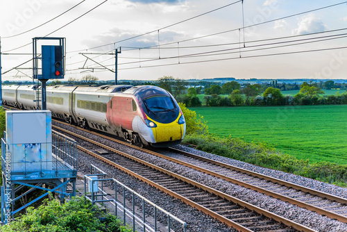 Obraz na plátně uk train railroad next to rapeseed field in bloom day view in england