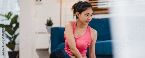 Ingelijste posters Ontspanning Young Asian woman practicing yoga in living room, attractive beautiful female working out for healthy at home. Lifestyle woman exercise concept. Panoramic banner background.