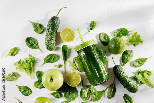 Cuadros en Lienzo  Green smoothie in cute glass jar shape of cactus with spinach and green fruits and vegetables on white table