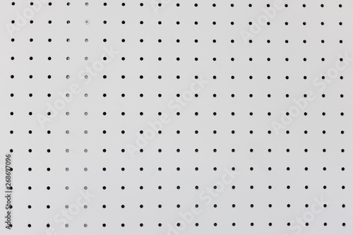 Fotografie, Obraz  orderly dot or holes rows and columns on white pegboard wall.