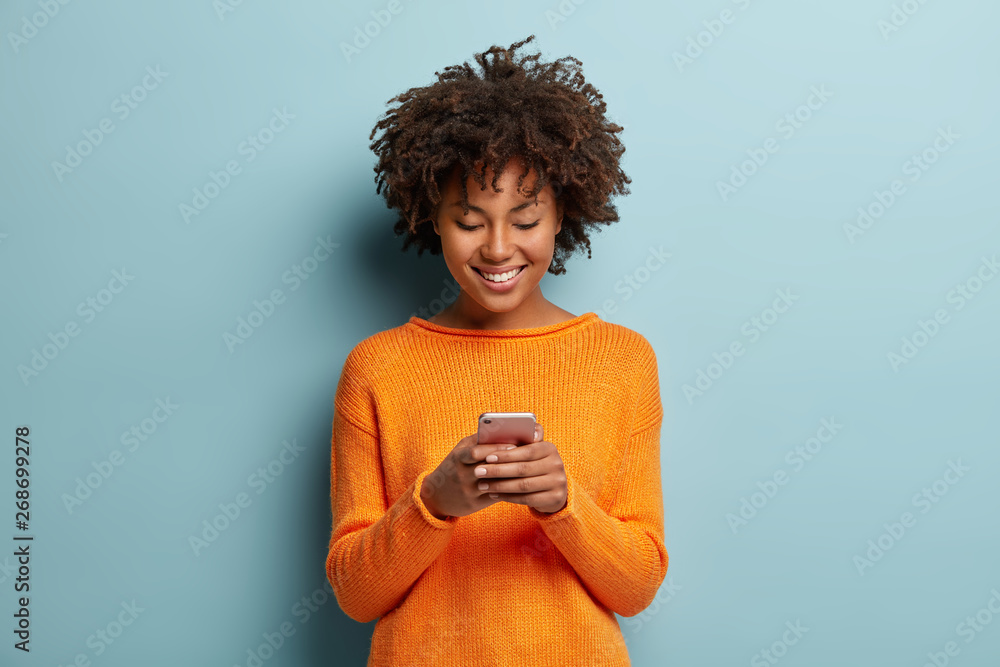 Fototapety, obrazy: Satisfied hipster girl with Afro haircut, types text message on cell phone, enjoys online communication, types feedback, wears orange jumper, isolated on blue studio wall. Technology concept