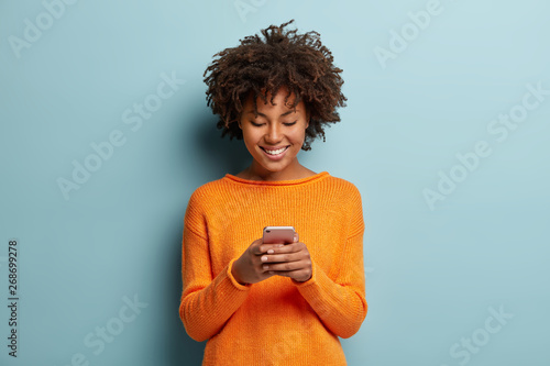 Fotografía Satisfied hipster girl with Afro haircut, types text message on cell phone, enjoys online communication, types feedback, wears orange jumper, isolated on blue studio wall