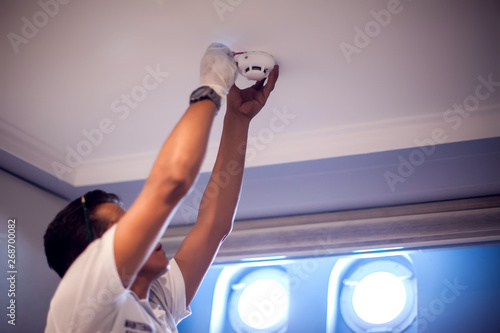 A man worker fix fire system on the ceiling Canvas-taulu