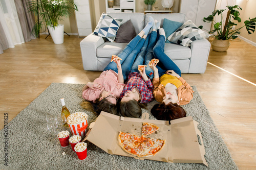 Aluminium Prints Three Girlfriends in jeans and shirts eating Pizza at home, lying on the floor and put legs on the sofa
