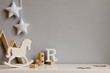canvas print picture - Stylish and cozy childroom with  wooden mountain box, horse, blocks and hanging white stars on the gray wall. Bright and sunny interior. Copy space. Minimalistic childish decor. Template.