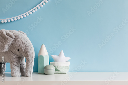 Cozy scandinavian newborn baby room with gray plush elephant ,white stars lamp and children accessories. Stylish interior with blue walls and haniging white garland. Template. Copy space.
