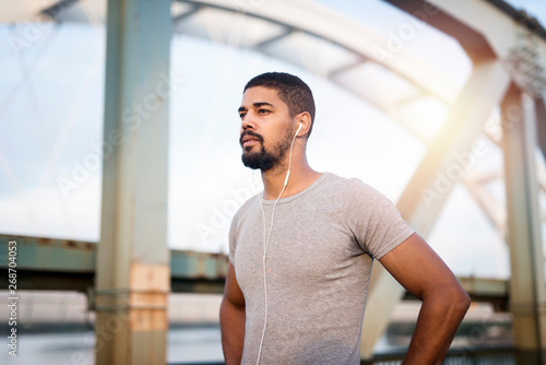 Portrait of handsome sportsman with earphones preparing for training Fototapet