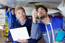 Mechanics Inspecting Underneath An Aircrafts Fuselage