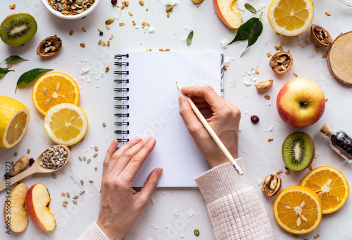 Fototapeta Female hand write in notebook on healthy food background, women diet nutrition recipe menu, fresh summer fruit granola seeds on white table organic super food, health care detox, top view, copy space obraz
