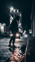 Back View Of Girl Walking On City Street At Night