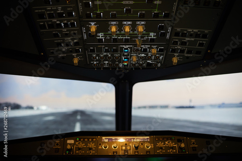 Airstrip view from airplane windshield, illuminated switches and knobs on dashbo Canvas Print