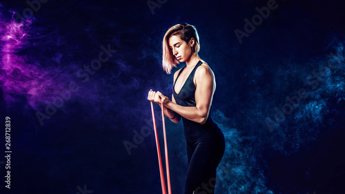 Valokuva  Sexy woman in sportswear using a resistance band in her exercise routine