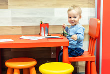 Cute Little Caucasian Blond Toddler Boy Sitting At Table And Drawing At Children Area At Retail Clothes Store. Baby Spending Time At Kid's Zone During Parents Shopping In Mall. Retailer Child Care