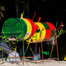 Jamaican Jerk Pan/ Grill In Rasta Colors In Jamaica. Used To Cook Jerk Fish, Chicken, Pork Meals Outdoors. It Is A Metal Drum Cut Down The Middle, Placed Sideways On Metal Stand, Filled With Coal.