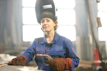 Waist Up Portrait Of Smiling Female Welder Posing Confidently While Working At Industrial Plant Or In Garage, Copy Space